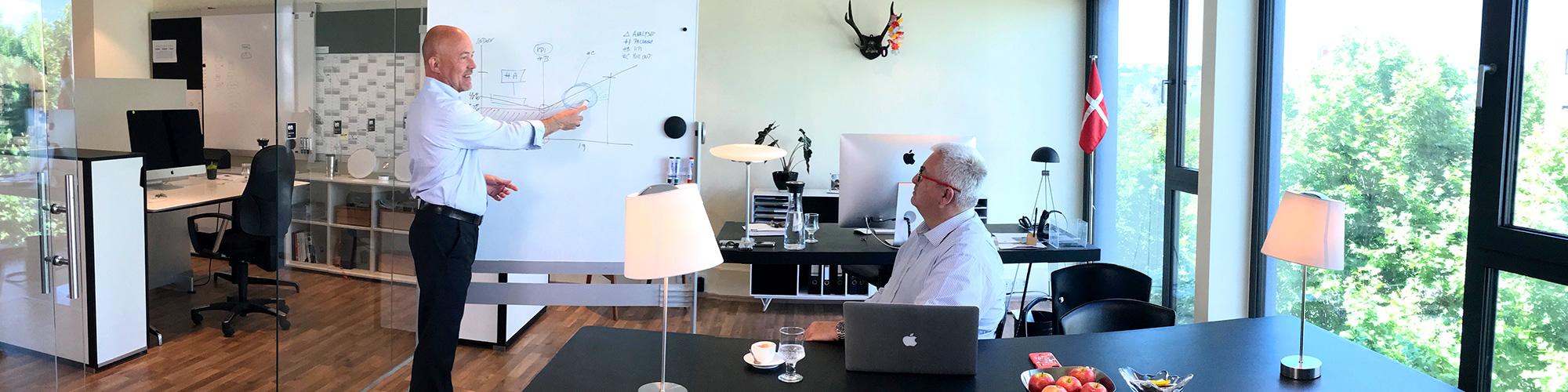 Beratungsszene: Berater erklärt etwas am Whiteboard während dessen der Kunde zuhört.